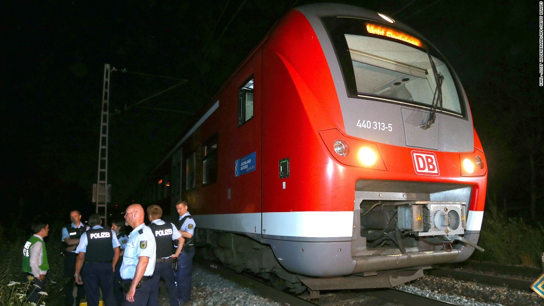Police stand by a regional train in Wurzburg, Germany, on Monday, July 18, after authorities said a man attacked passengers with an ax. German police shot the man dead in a confrontation after he fled the train. Four passengers who were attacked are in serious condition, police said.