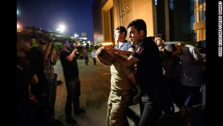 Turkish police escort an accused coup participant from an Istanbul courthouse last month.