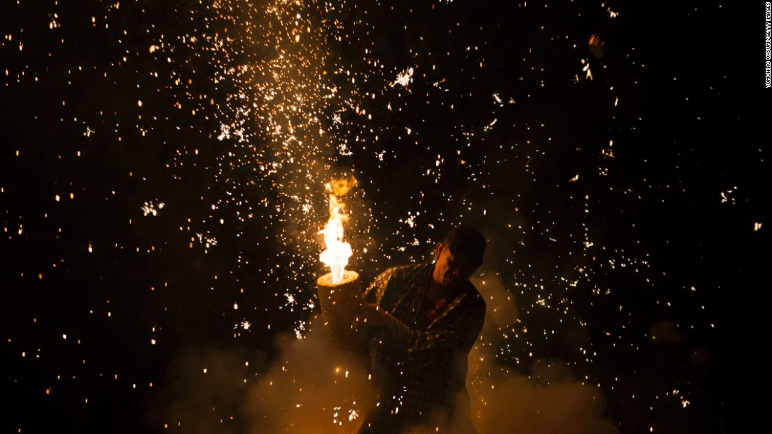 A pyrotechnician holds a bamboo cylinder containing fireworks during the Gion Festival in Toyohashi, Japan, on Friday, July 15.