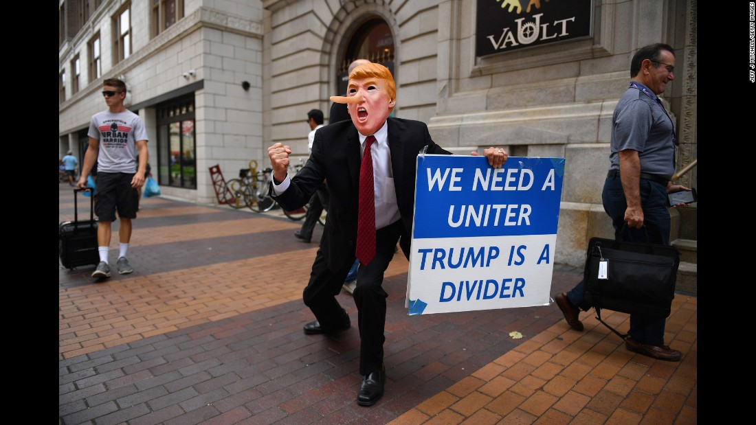 A man wearing a Donald Trump mask walks through downtown Cleveland on Sunday, July 17.