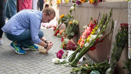 People lay flowers and candles outside the OEZ shopping center the day after a shooting spree left nine victims dead on Saturday, July 23 in Munich, Germany.