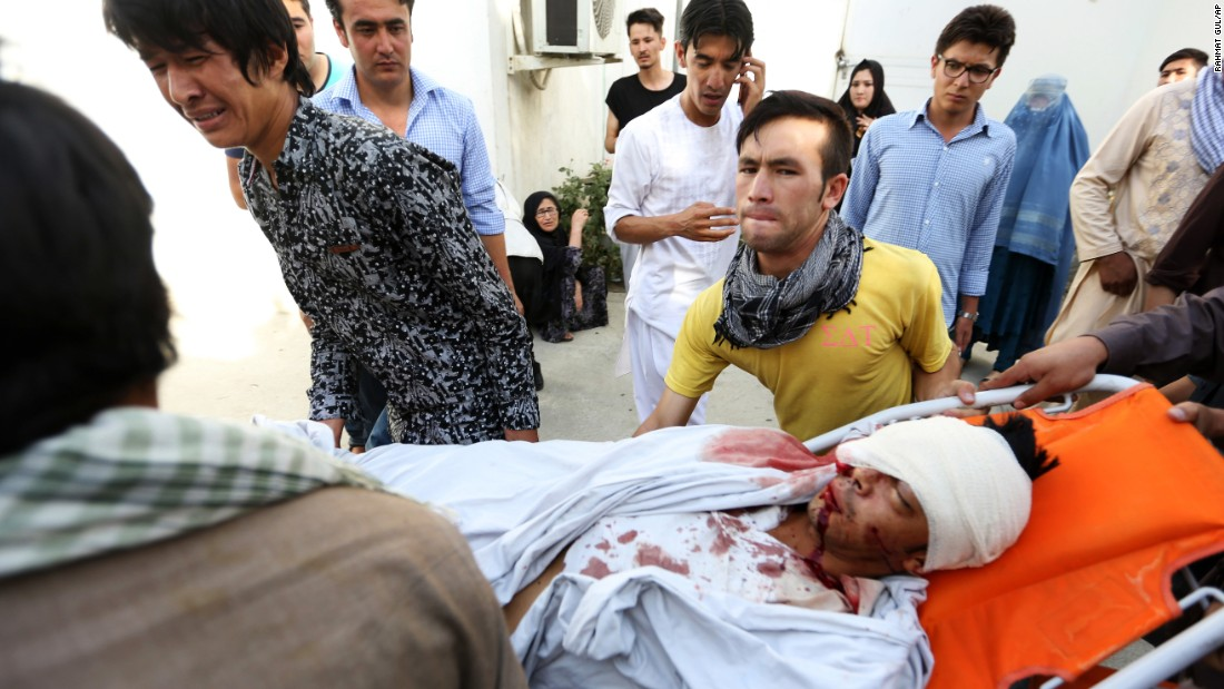 Afghans help a man who was injured in the deadly explosion.