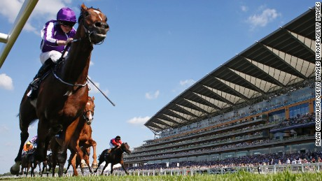 Ryan Moore riding Highland Reel races towards the line in The King George VI And Queen Elizabeth Stakes at Ascot Racecourse.