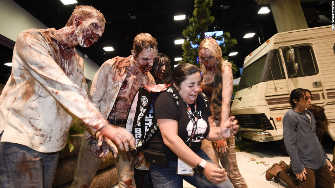 "Martha Guzman screams as she poses for a photo with zombies at ""The Walking Dead"" booth."