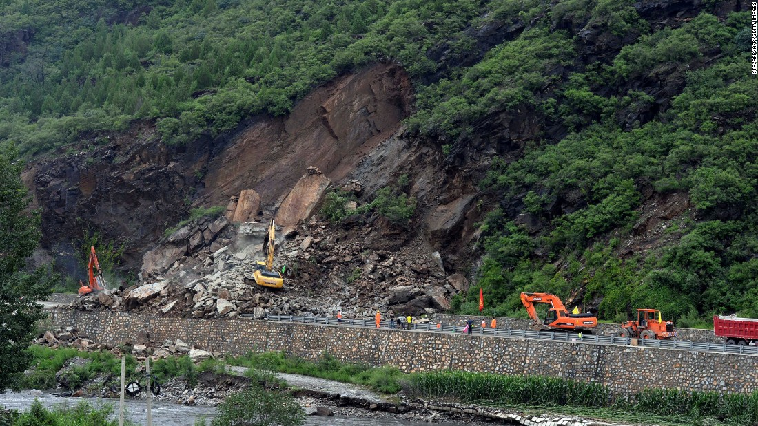 This photo taken on July 21, 2016 shows workers repairing a damaged road hit by heavy rainstorms in Fangshan District in Beijing.
