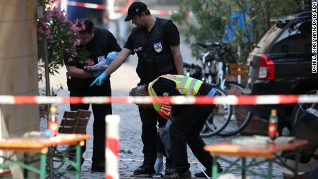 Police officers conduct an investigation on Monday, following a suicide bombing in Ansbach, Germany.