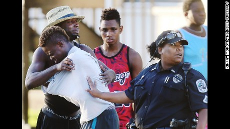 People embrace after a fatal shooting at Club Blu in Fort Myers, Fla., Monday, July 25, 2016. (Kinfay Moroti/The News-Press via AP)