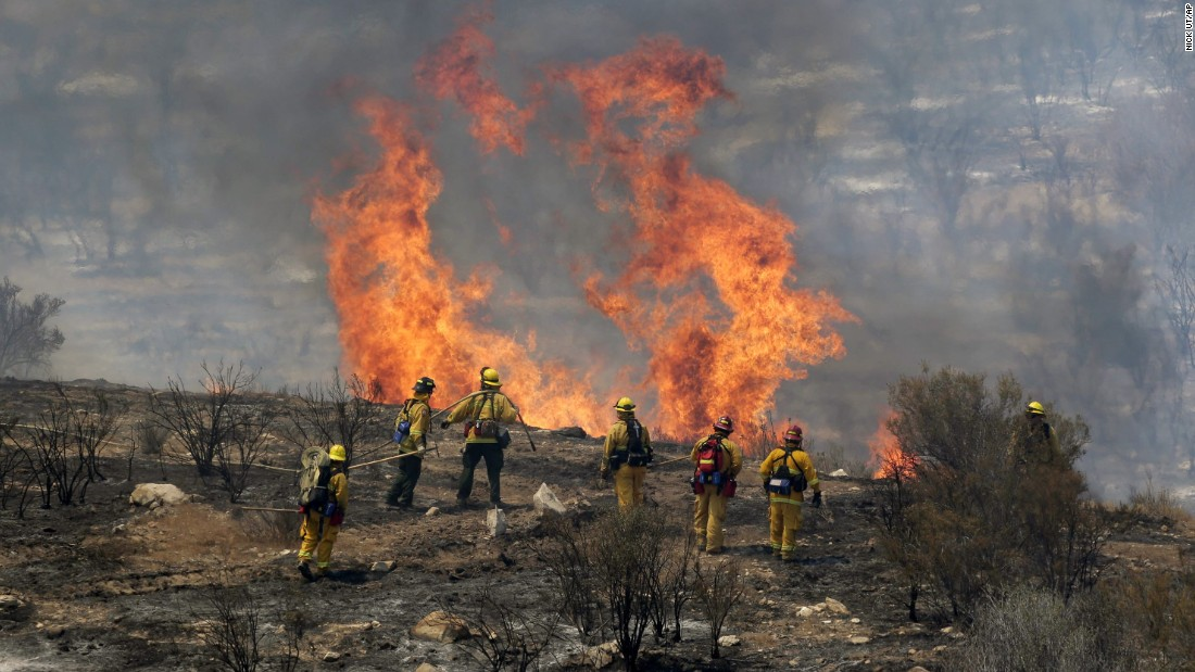 Firefighters monitor a flareup as they work to stop the advance of the Sand Fire near the town of Acton, California.