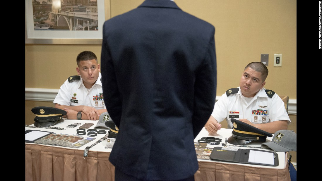 U.S. Army recruiters speak to a job-seeker during a career fair in Houston on Thursday, July 7.