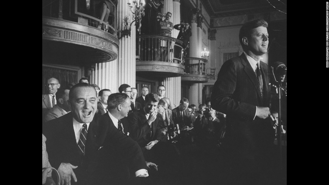 Johnson, left, and Robert F. Kennedy, center, share a laugh during remarks by John F. Kennedy.<br />