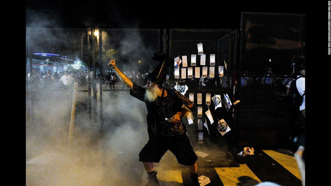 Performance artist Vermin Supreme stands by the gates to the convention after an American and Israeli flag were burned by protesters.
