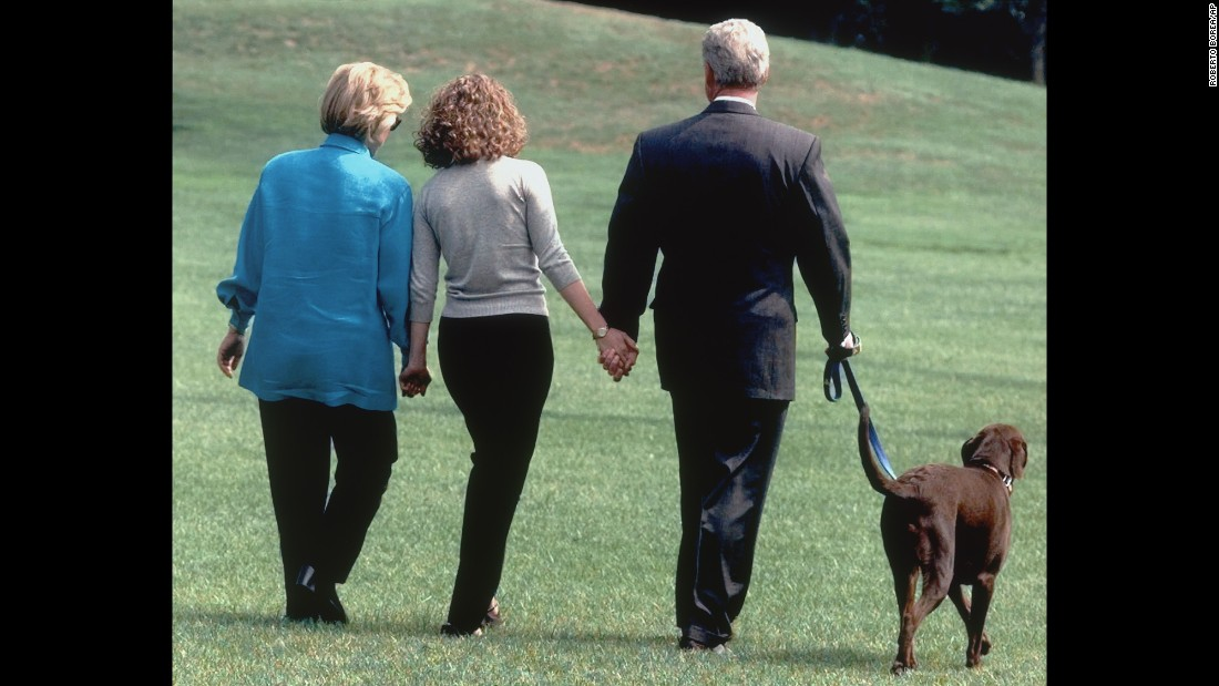 The first family walks with their dog, Buddy, on the White House lawn in August 1998.