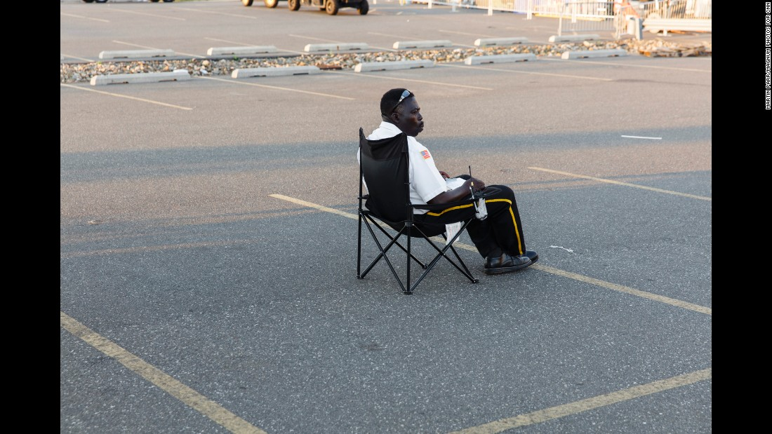 A security guard sits in a parking lot past the media entrance to the convention grounds.