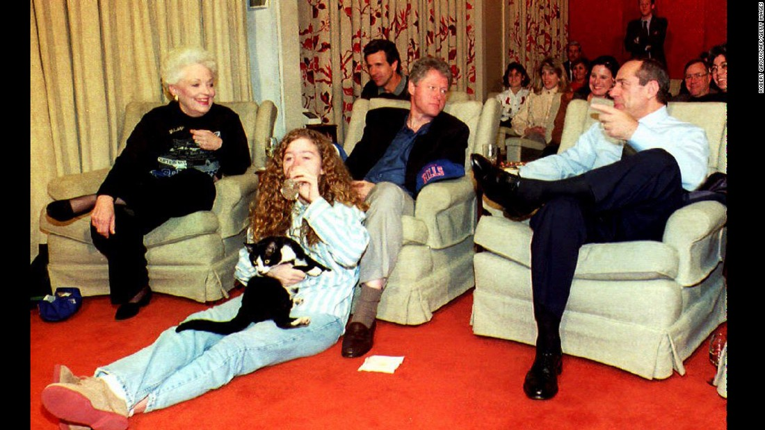 Clinton chats with former New York Governor Governor Mario Cuomo, while daughter Chelsea Clinton cuddles Socks at the White House in 1993.