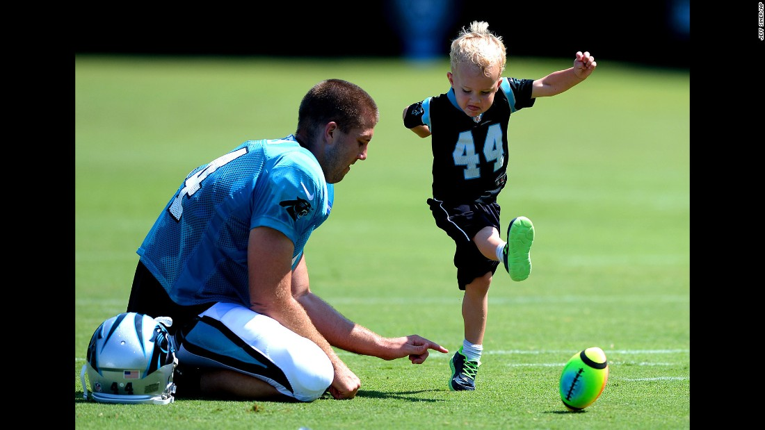 Carolina long snapper J.J. Jansen holds the ball for his son, Luke, after a training-camp practice in Spartanburg, South Carolina, on Sunday, July 31.