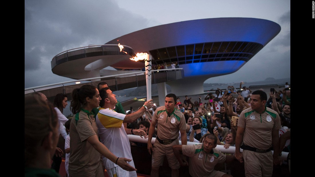 The Olympic torch is carried past the Contemporary Art Museum in Niteroi, Brazil, as it makes its way to Rio on Tuesday, August 2.