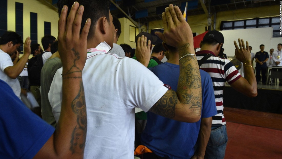 Some 1,000 people whom authorities accused of being drug users and dealers take an oath before local authorities after turning themselves in in Tanauan, the Philippines, on July 18, 2016.