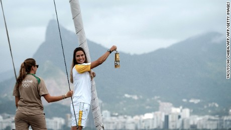 Brazilian sailor Isabel Swan (R) holds the Olympic flame on a yacht heading from Niteroi to Rio de Janeiro passing through Guanabara Bay on August 3, 2016 ahead of the Rio 2016 Olympic Games in Rio de Janeiro. / AFP / YASUYOSHI CHIBA        (Photo credit should read YASUYOSHI CHIBA/AFP/Getty Images)
