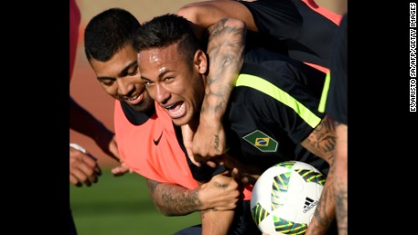 Brazilian footballers Neymar (R) and Gabriel Jesus joke during a training session.