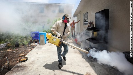 Carlos Varas, a Miami-Dade County mosquito inspector, sprays around homes in the Wynwood area of Miami.