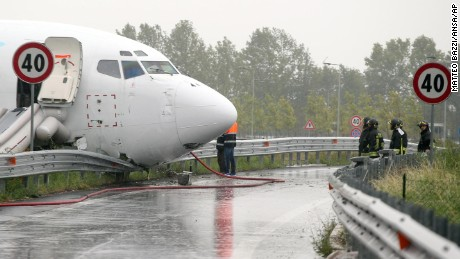 Firefighters work on a DHL cargo plane that skidded off a runway overnight at the airport of Bergamo Orio al Serio in northern Italy, crashing through a guard rail onto a highway on Friday, August 5.