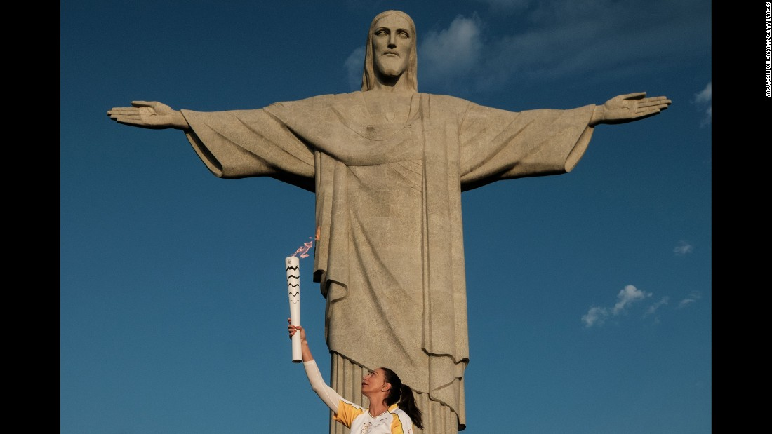 Retired Brazilian volleyball player Maria Isabel Barroso Salgado carries the Olympic torch in front of the Christ the Redeemer statue in Rio de Janeiro on Friday, August 5. The opening ceremony will be held at the Maracana Stadium on Friday night.