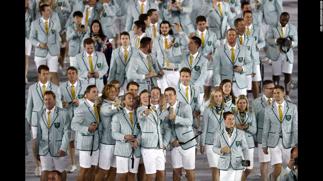 Members of Australia's Olympic team take photos inside the stadium.