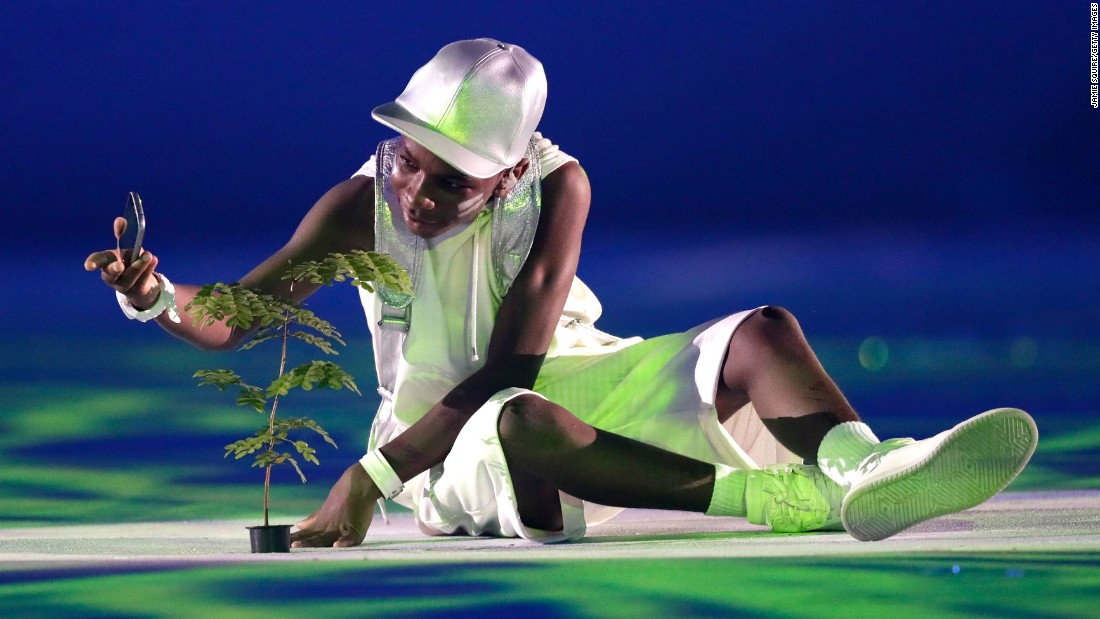 A performer holds a plant. The ceremony was designed to promote two messages: protection of the environment and peace.