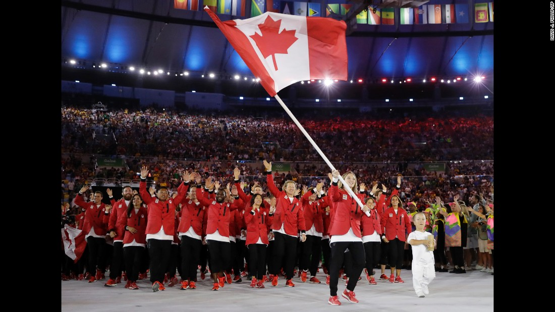 Trampoline gymnast Rosie MacLennan carries the Canadian flag.