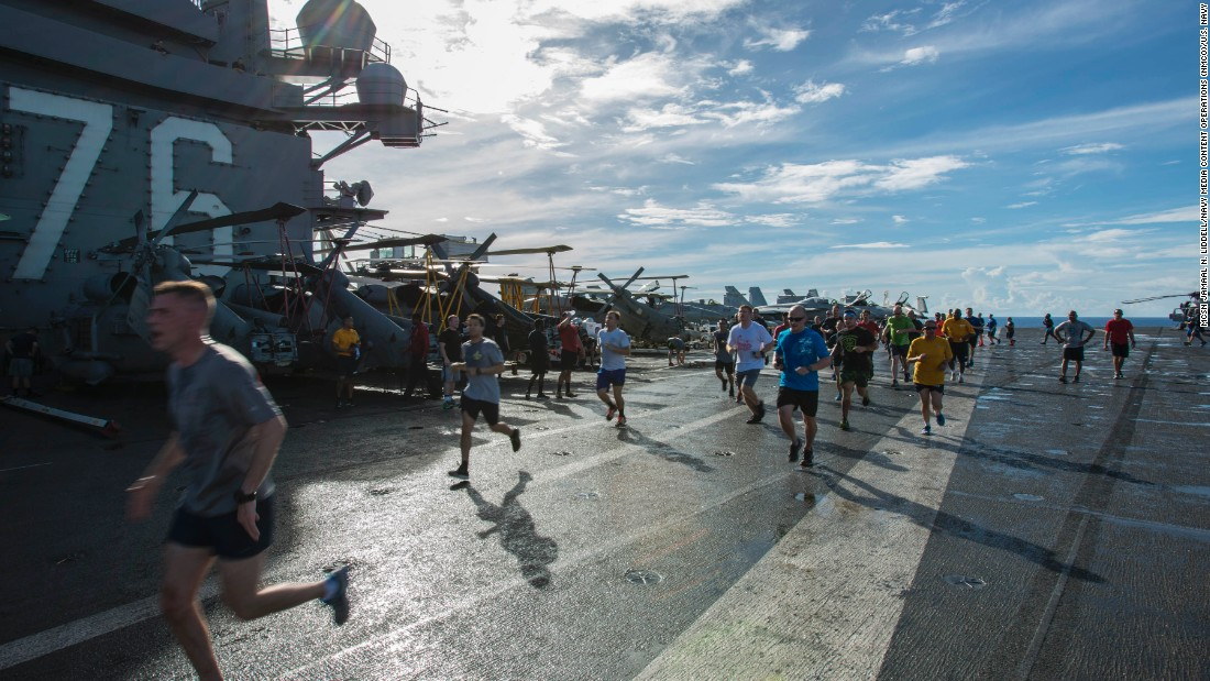 "The ""rubber duckies"" are kept in fanny packs and pulled out and put over the head in an emergency. Here, crew run a 5K on the deck of the USS Ronald Reagan."