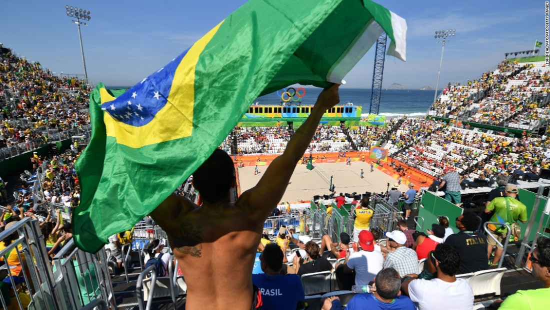 A Brazilian fan waves the national flag during the first day of the Olympic beach volleyball competition. Security checks meant long queues for those entering, and left the venue looking half empty for the early matches.