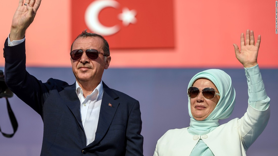 Erdogan (L) an his wife Emine Erdogan (R) wave at supporters at the rally.