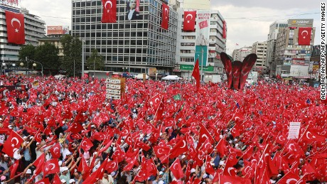 People wave Turkish national flags as they gather in Ankara during a rally against the failed military coup.