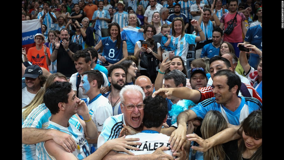 Volleyball player Demian Gonzalez is embraced by Argentina fans after his team beat Russia in a preliminary round. They will next face Poland on Thursday.