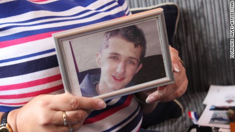 Lynne Sandford holds a photo of her son; if convicted, she hopes he can serve his sentence in the UK.