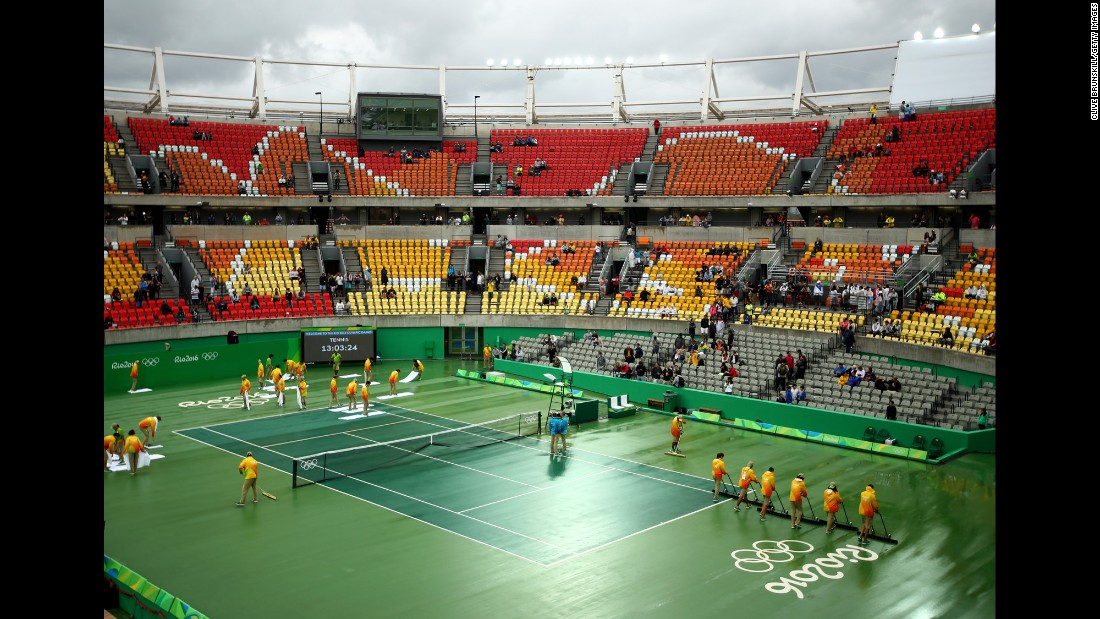 Volunteers dry a rain-soaked court at the Olympic Tennis Center.