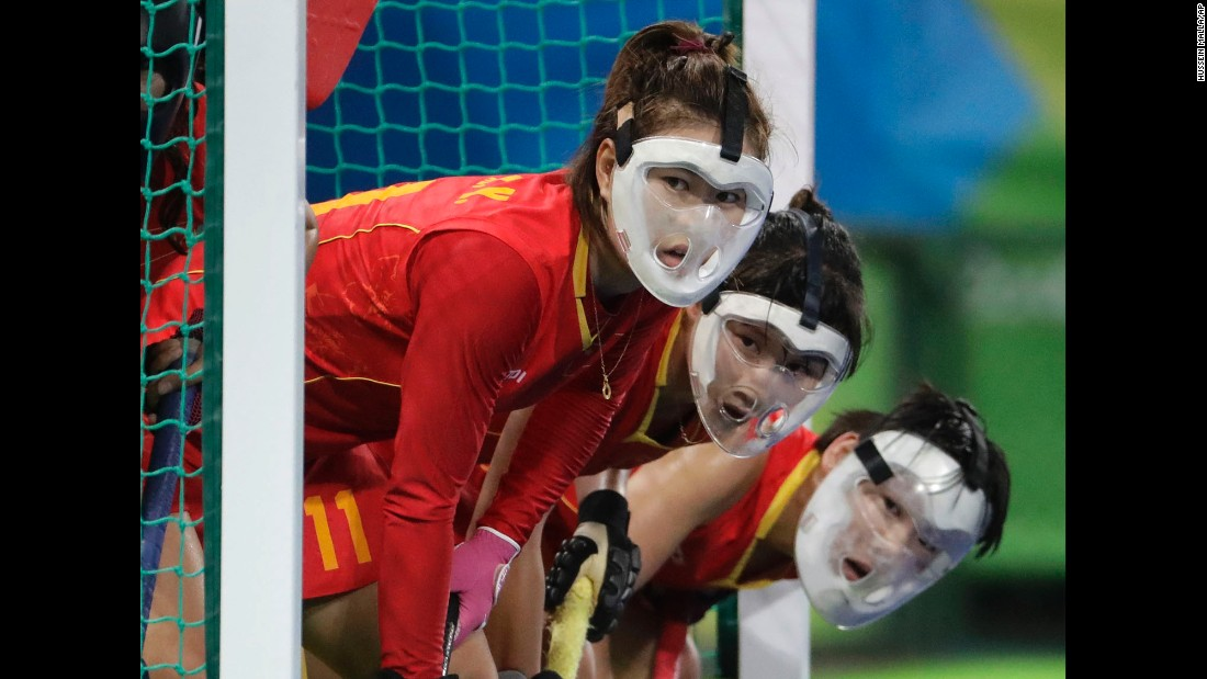 Chinese field hockey players wear protective face masks as they wait for a corner shot from the Netherlands.