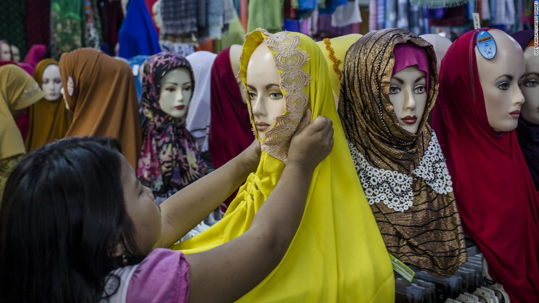 <strong>Hijab:</strong> The scarf worn tightly around the head and neck does not cover the face. It is the most common Islamic head covering. This Indonesian girl is shopping for a hijab in Yogyakarta.