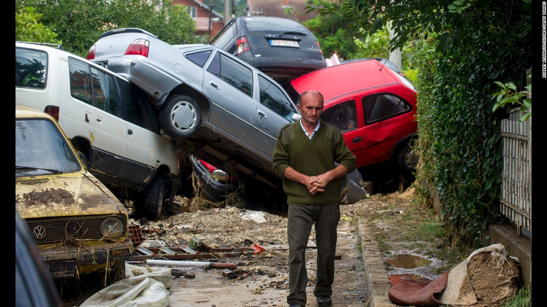 "A man passes damaged vehicles in Stajkovci, Macedonia, after flash flooding on Sunday, August 7. Authorities <a href=""http://www.cnn.com/2016/08/07/europe/macedonia-storms/"" target=""_blank"">declared a crisis</a> after powerful storms left at least 21 people dead, state-run media said."