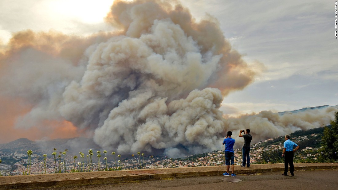 "People take pictures of the smoke rising from <a href=""http://www.cnn.com/2016/08/11/europe/europe-france-spain-portugal-wildfires/index.html"" target=""_blank"">a wildfire on Portugal's Madeira Island</a> on Tuesday, August 9."