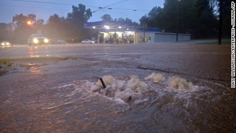 Floodwaters surge from a crack in the parking lot on the corner of highways 584 and 51 in Osyka, Miss., early Friday, Aug. 12, 2016. Flooding is also affecting areas of southwest Mississippi just north of the Louisiana state line.  (Matt Williamson/Enterprise-Journal via AP