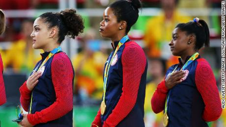 RIO DE JANEIRO, BRAZIL - AUGUST 09:  (R to L) Gold Medalists Simone Biles, Gabrielle Douglas, Lauren Hernandez, Madison Kocian and Alexandra Raisman of the United States stand on the podium for the national anthem at the medal ceremony for the Artistic Gymnastics Women's Team Final on Day 4 of the Rio 2016 Olympic Games at the Rio Olympic Arena on August 9, 2016 in Rio de Janeiro, Brazil.  (Photo by Alex Livesey/Getty Images)