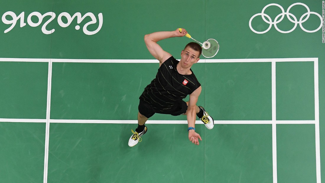 Poland's Adrian Dziolko serves to China's Chen Long during their singles qualifying badminton match.