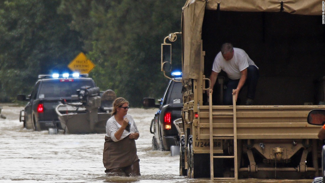 Jeff Robinson lowers a ladder from a National Guard truck as his wife wades through floodwaters near their home in Baptist, Louisiana, on August 13.