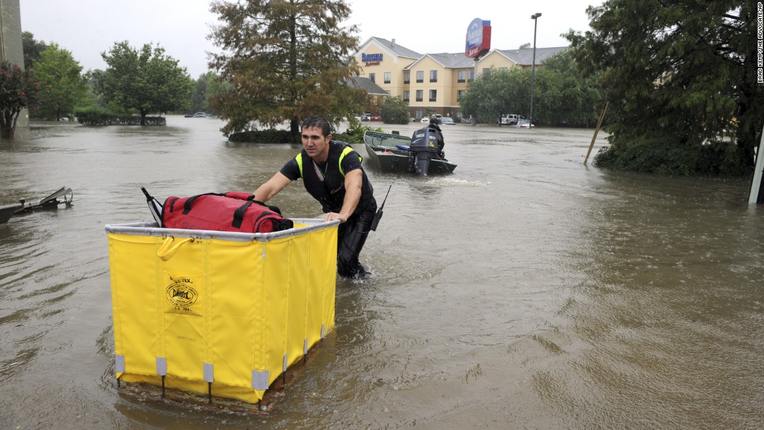A firefighter brings luggage to hotel guests during an evacuation of the Fairfield Inn in Lafayette, Louisiana, on August 13.