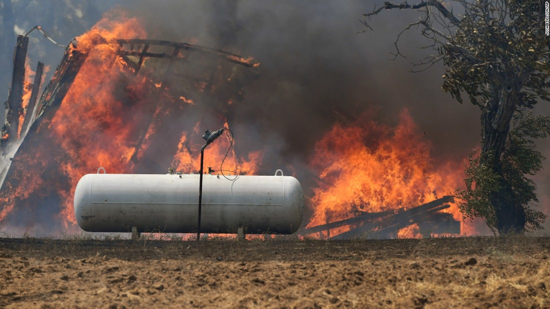 Flames approach a propane tank near the town of Lower Lake, California.