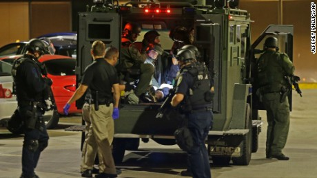 Police officers take an injured man in an armored vehicle to a hospital.