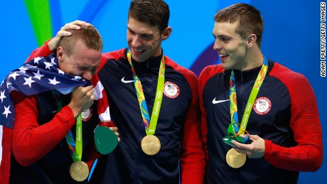 Members of the men's 4 x 100m Freestyle Relay team, including Michael Phelps, with their medal-holders.