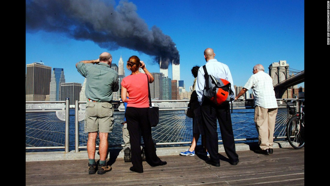 Pedestrians look across the East River to the burning towers.