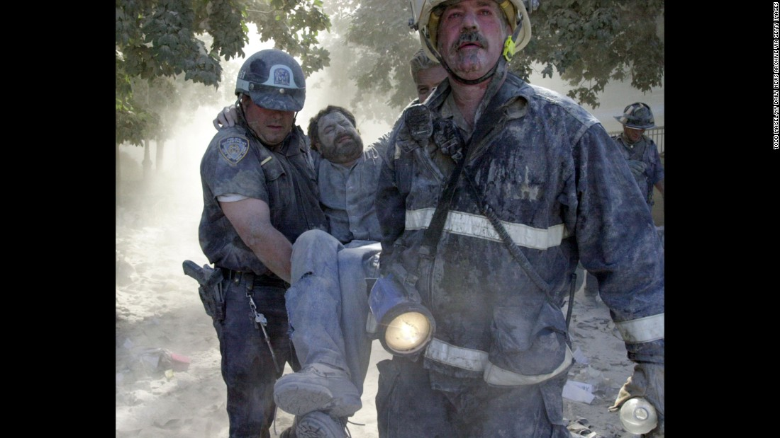 New York Daily News photographer David Handschuh is carried after his leg was shattered by falling debris.